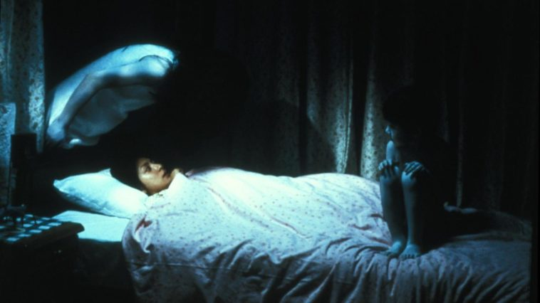 A person lays in bed with two horrifying figures surrounding them, haunting them.