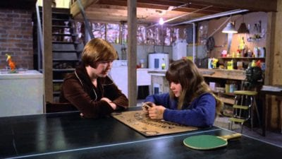 a mother and daughter sit at a ping pong table in a basement with a ouija board between them - still shot from the Exorcist