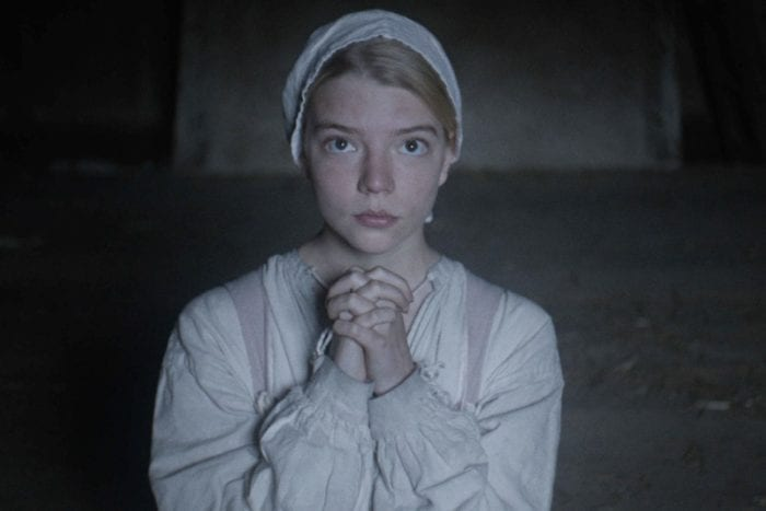 A young woman dressed in period clothing, holds her hands in prayer.