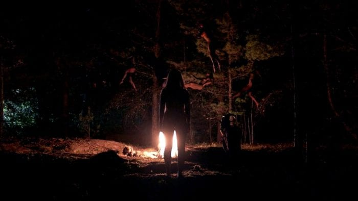 The shadow of a young woman is in the woods approaching a fire in the center of a circle.