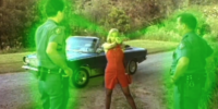 A woman holds up a tube of lipstick that shoots green beams at two police officers that stand in front of her.