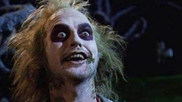 Close frame of Beetlejuice, with messy green hair, green mold on skin, and blackened eyes, looks excitedly into the camera.