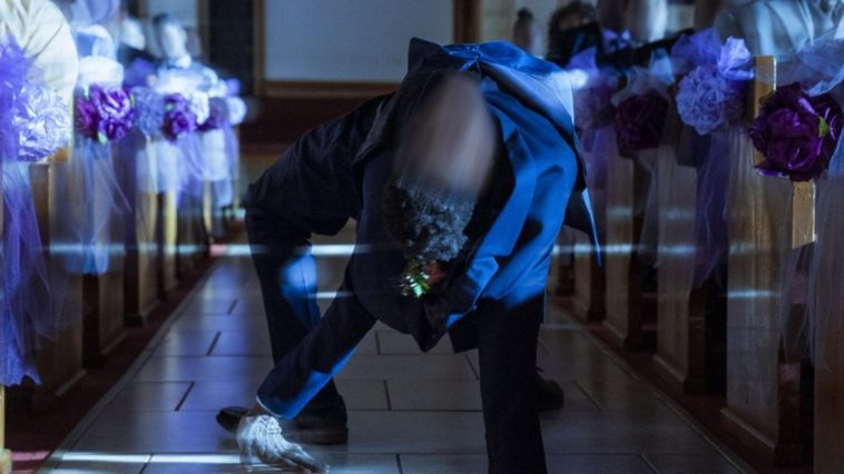 Person with a blurry face spider walking down the aisle of a church
