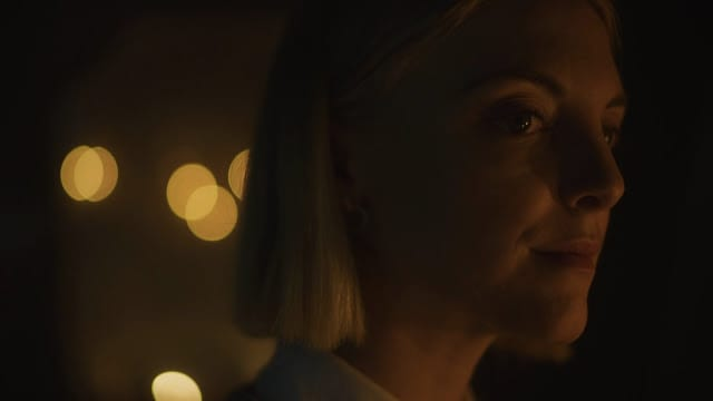 Emily (Lauren Beatty) looks confidently, lit by firelight.