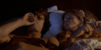 Bob lies in bed, his bare chest exposed, taking a drag from his cigarette; lying next to him, unlit cigarette in her hand, Lynda looks over at him.
