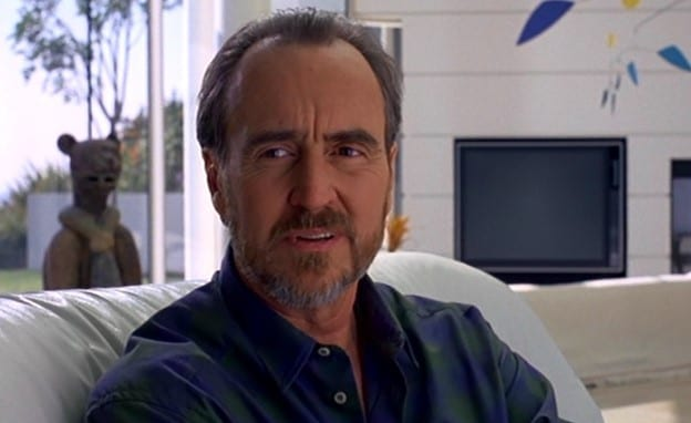 Wes Craven, receding hairline and salt and pepper goatee, wearing a button-up, collared shirt with the top buttons unbuttoned, sits on his couch and looks just off-camera with an expression that suggests worry.