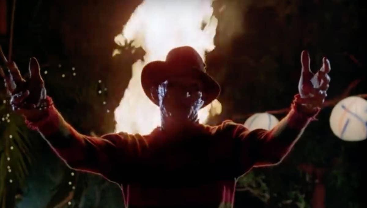 Freddy Krueger, clad in his usual green and red sweater and brown fedora, holds his arms outstretched while a roaring fire blazes behind him.