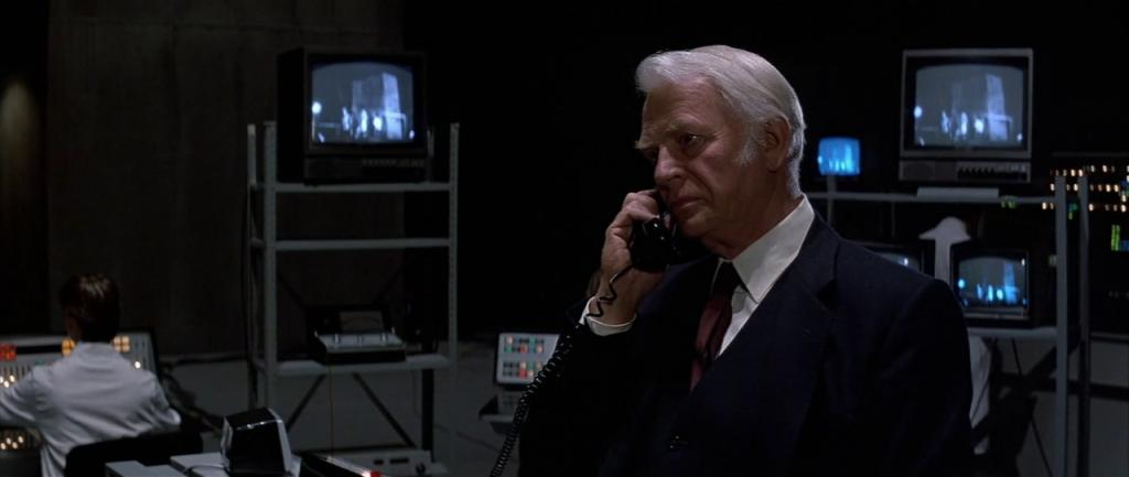 In the foreground, Conal Cochran, white-haired and dressed in suit and tie, holds a phone to his ear; in the background, we see several TV monitors and a man in a white lab coat sitting in front of what appears to be some kind of control panel.