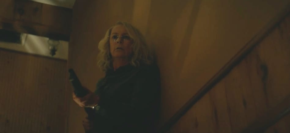 Jamie Lee Curtis descends a staircase holding a gun.
