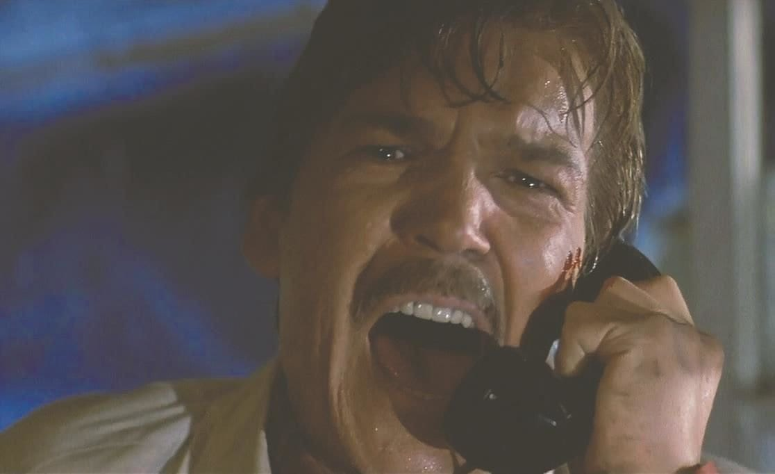 A close-up of the mustachioed face of Tom Atkins; his wet hair hangs down onto his forehead and his mouth is wide open in a scream as he yells into the phone that he holds to his ear.