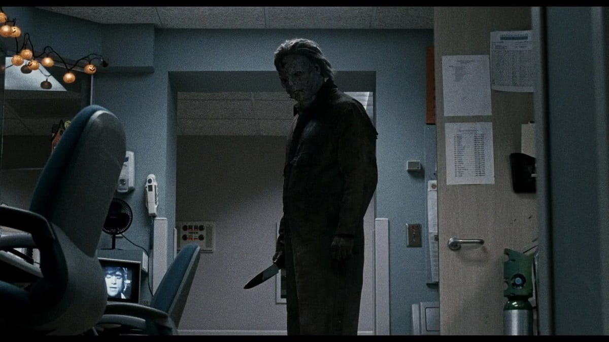 Michael Myers stands wielding a knife, admiring a recent kill with a deathly stare.