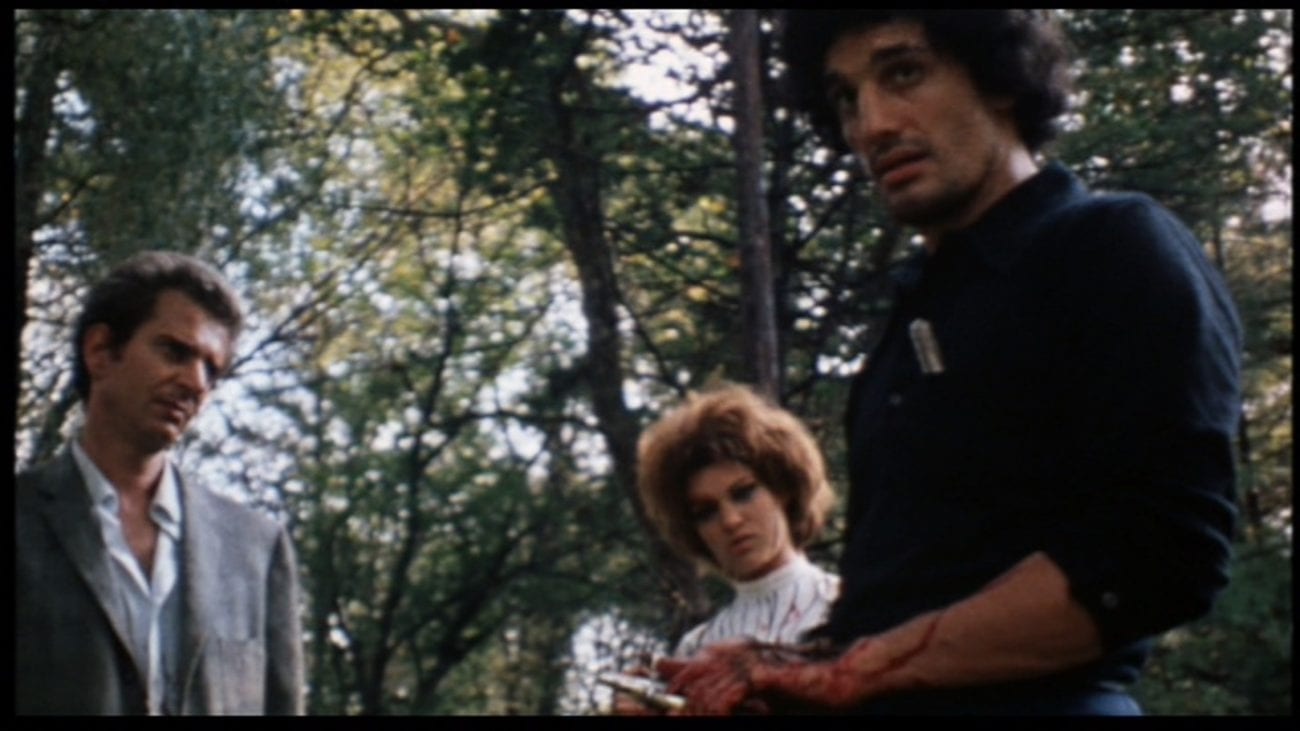In the foreground, Krug, a dark-haired man with the sleeves of his shirt rolled up and what looks like blood on his hand and forearm, holds what appears to be a knife and looks offscreen. Behind him, his compatriots, a man in an unbuttoned suit jacket and a woman with big hair look, respectively, at Krug and down at something offscreen.