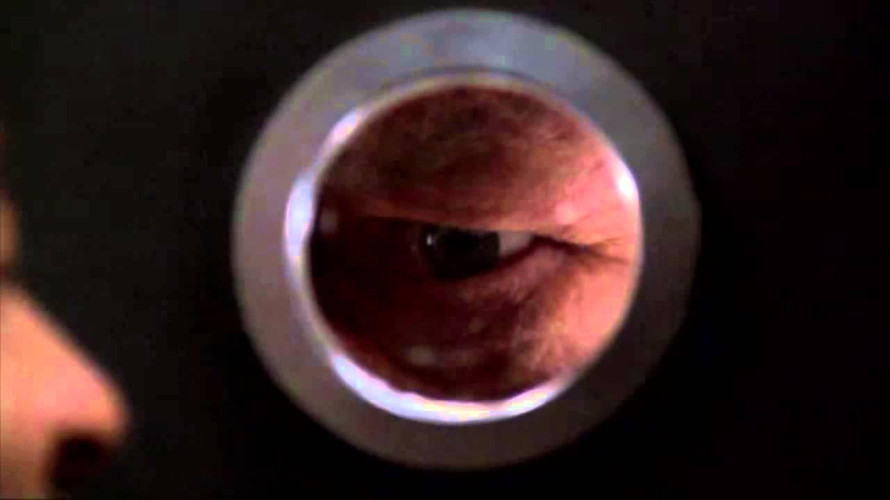 Pratt looking through peephole at Mr. White