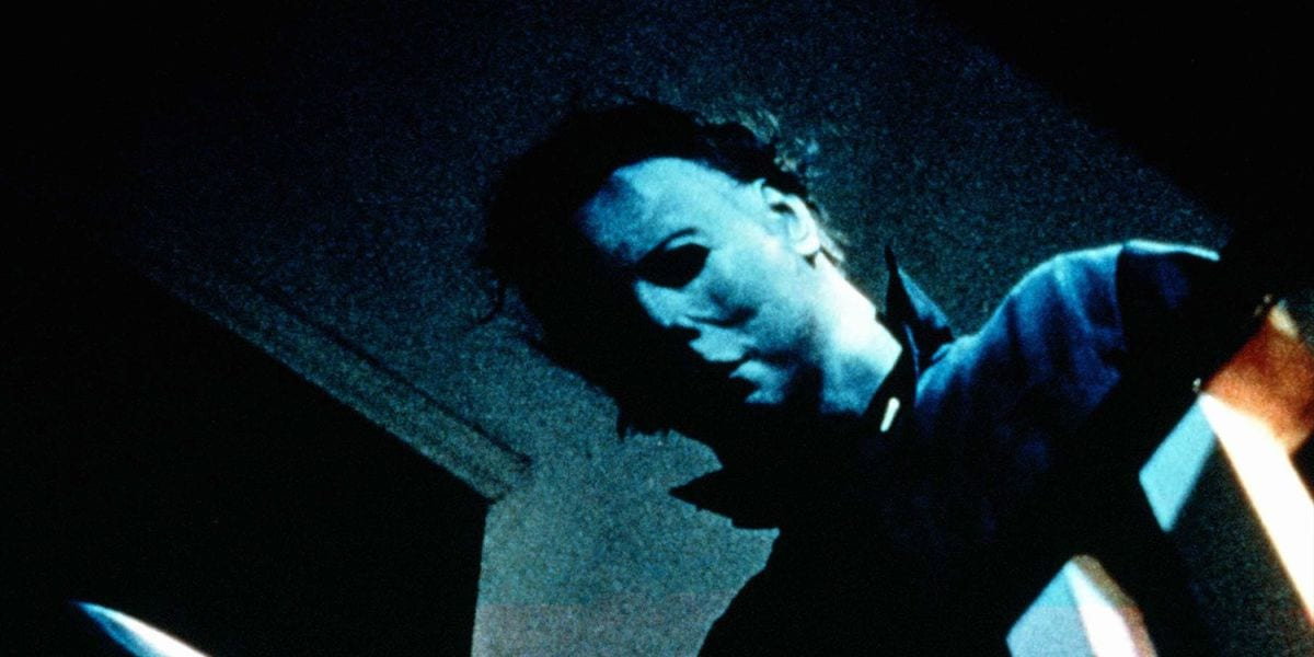Michael Myers, half his pale white mask covered in shadow, peers over the railing at the top of the stairs; just visible at the bottom of the frame is the tip of the knife he holds in his right hand.