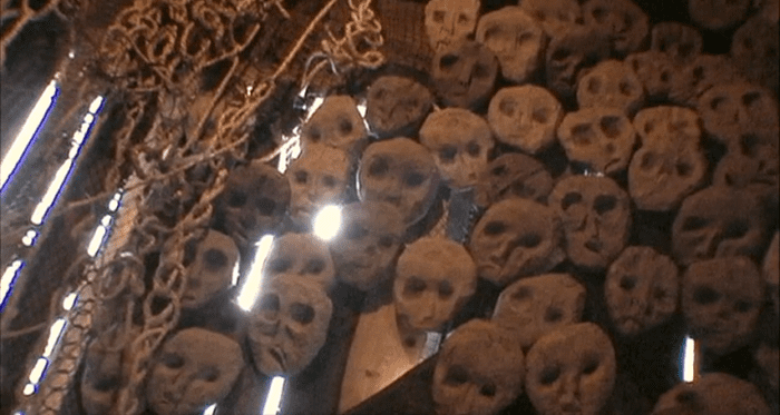 A bunch of masks hang from a wall