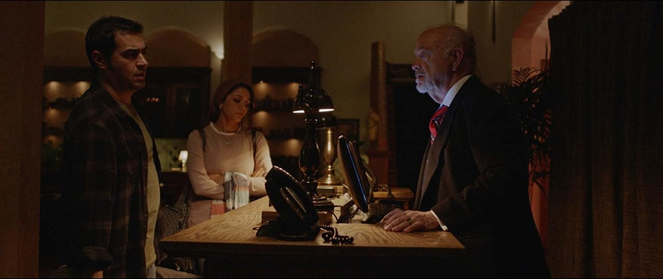 A man and a woman check in at a hotel as the clerk looks at them intently.