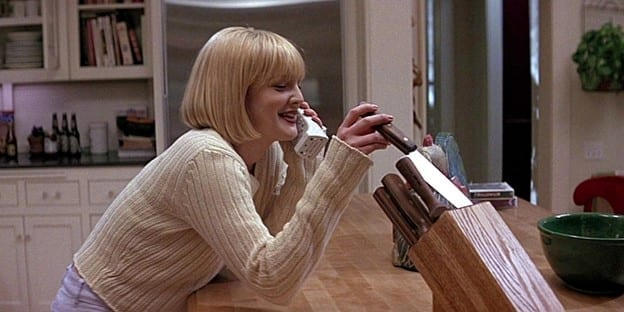 Drew Barrymore, in blonde wig, smiles and pulls a knife from the knife block as she talks to an unknown caller on a cordless phone.