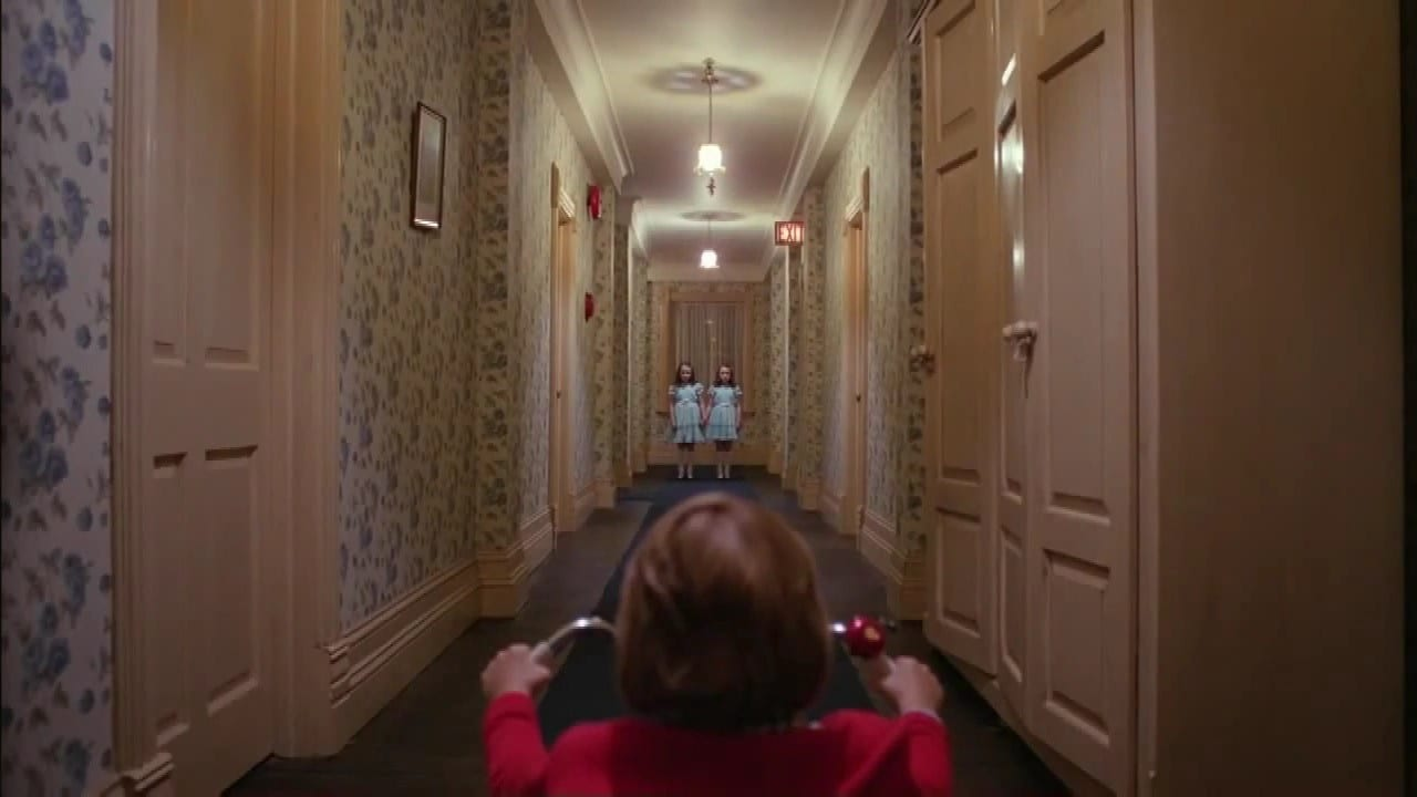 In the foreground and from behind, we see a young boy, hands on the handle grips of his tricycle; a long hallway, with closed doors on each side, stretches away from him and into the far background, where we see two small girls, wearing identical dresses and standing side by side.
