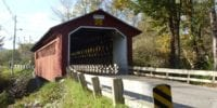 A red covered bridge in a rural area.