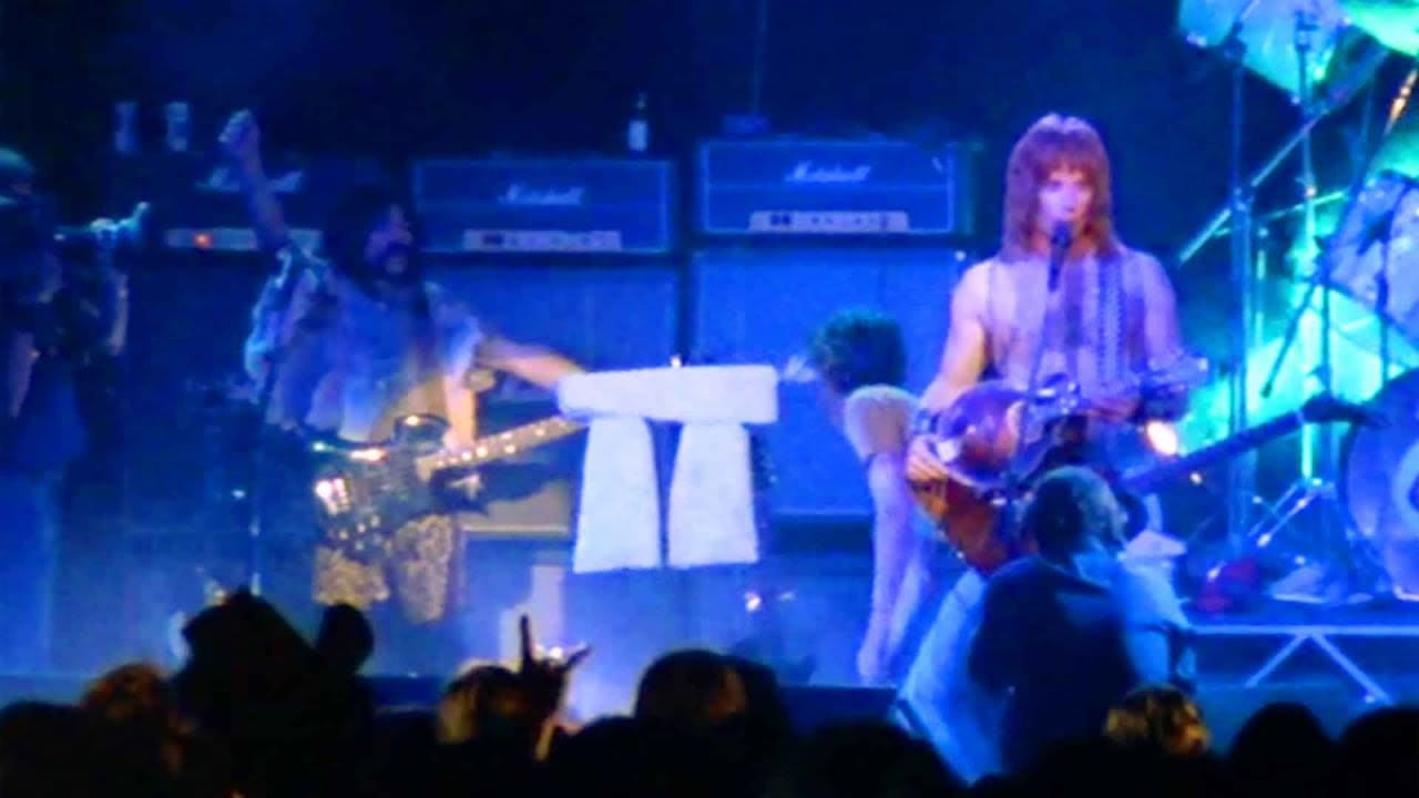 Two longhaired men, one with a guitar and the other with a bass, stand on stage, microphones in front of them; hanging between them, being lowered onto the stage, is a mini-Stonehenge monument.