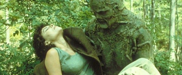 A large, green humanoid carries an unconscious woman in his arms through swampland.