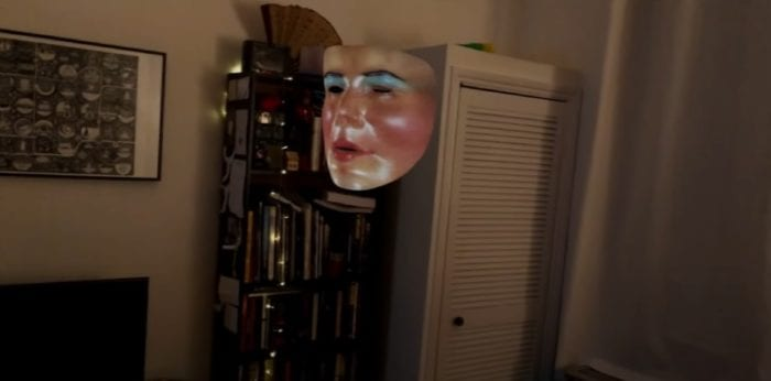 A dimly lit off-white room. A floating pale face with heavy blush, red lips, blue eyes, and no eyeballs rests in front of a dark bookshelf.
