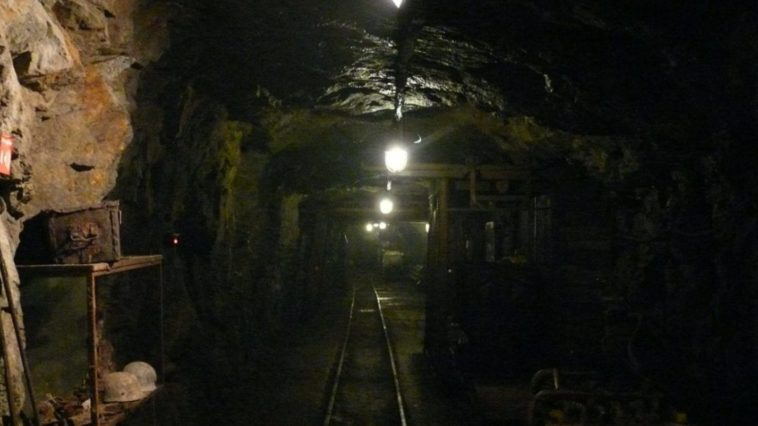 An underground mine, illuminated by overhead lights. Tools are scattered on shelves on either side of a central tunnel.