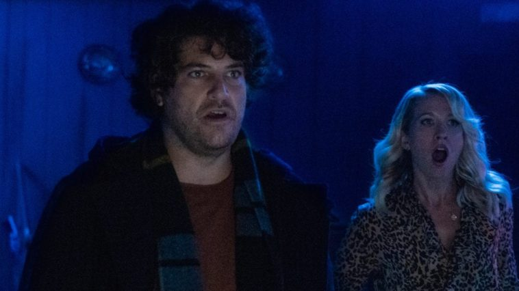 Adam Pally stands front with a shocked look on his face while Anna Camp stands behind him terrified in a dark blue room.