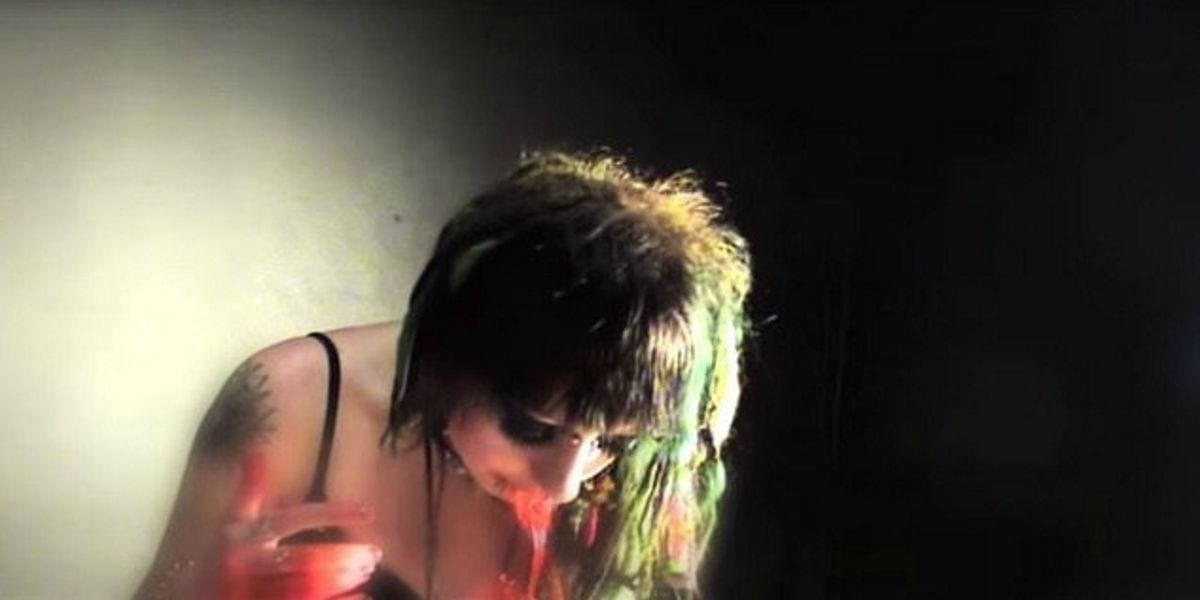 A slightly grainy image of a pale girl, her head hanging down while a red substance spills from her mouth. She has a tattoo on her right shoulder and is wearing a black tank top. Her hair, a mixture of mint green and deep brown, is partially illuminated by light coming from the right side of the image. The right side of the background is pitch black while the left is a dirt off white color, seemingly lit by the same light off to the right.