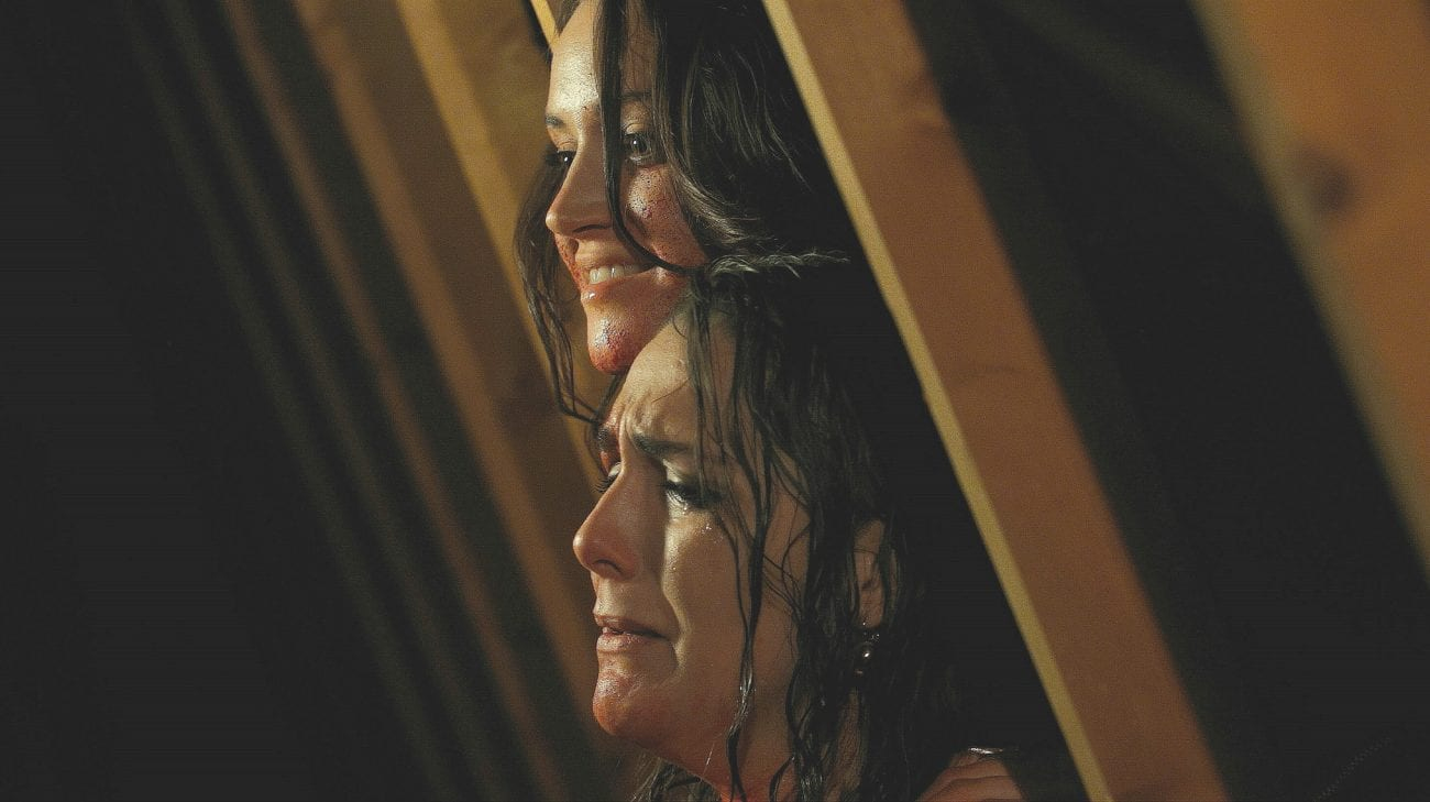 A possessed Lucy holds a terrified Lauren in the attic