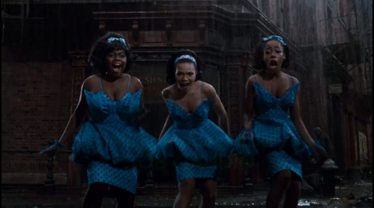 """Ronette (Michelle Weeks), Chiffon (Tisha Campbell), and Crystal (Tichina Arnold) dance across the street in matching blue outfits, singing to the audience without getting wet, in the film, """"Little Shop of Horrors"""" (1986)."""