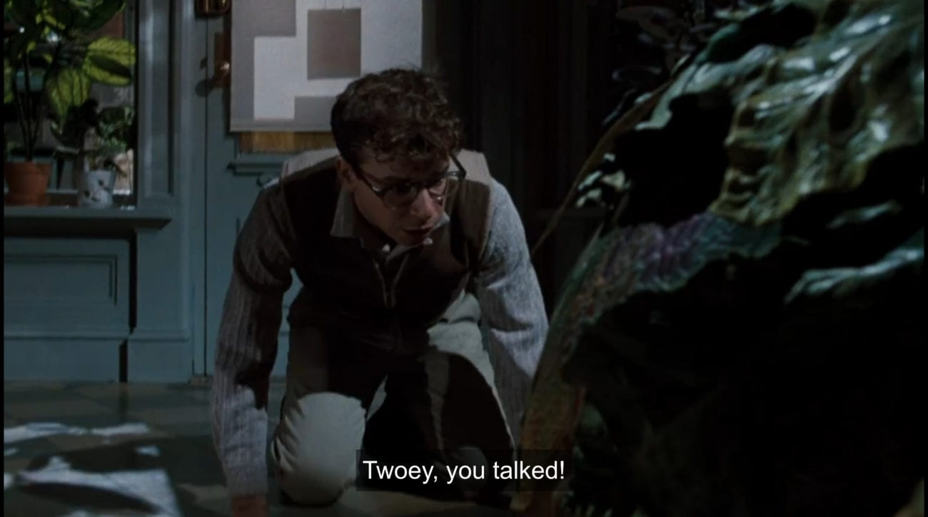 """Seymour Krelborn (Rick Moranis) kneels in front of carnivorous plant Audrey II, exclaiming, """"Twoey, you talked!"""", in the film, """"Little Shop of Horrors"""" (1986)."""