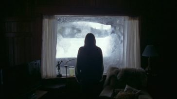 Grace looks out a frosted over window