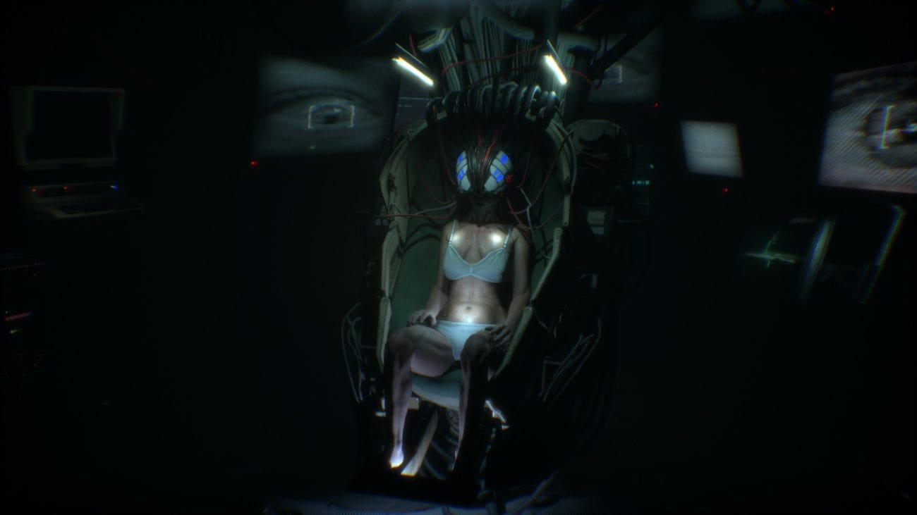 A woman in her underwear sits in a domed chair. She is wearing a helmet is many wires leading up into the ceiling