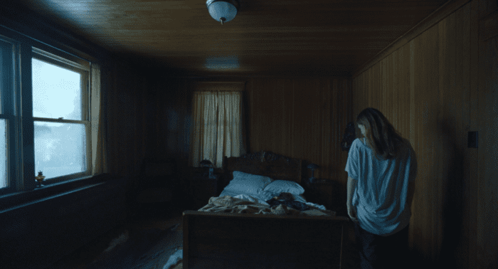 Grace looks down at an unmade bed in The Lodge