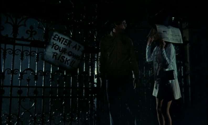 "Brad Majors (Barry Bostwick) and Janet Weiss (Susan Sarandon) stand in the rain next to a sign that says, ""ENTER AT YOUR OWN RISK!!"", in the film, ""The Rocky Horror Picture Show"" (1975)."