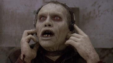 A zombie listens to something through headphones.