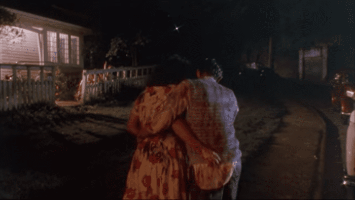Paquita and Lionel walk away from the camera arm in arm