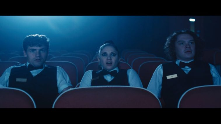 Ricky (pale boy with thick brows and short dark hair), Chaz (pale girl with heavy eyeliner and dark hair tied back in a ponytail), and Abe (husky pale boy with shoulder-length fuzzy dark hair) sit in a vacant theater watching the cursed film reel. They all wear black vests adorned with golden nametags atop white dress shirts, and black bowties. They are illuminated from behind by the soft blue projector light. They all appear concerned, Chaz especially, her mouth agape and eyes wide.