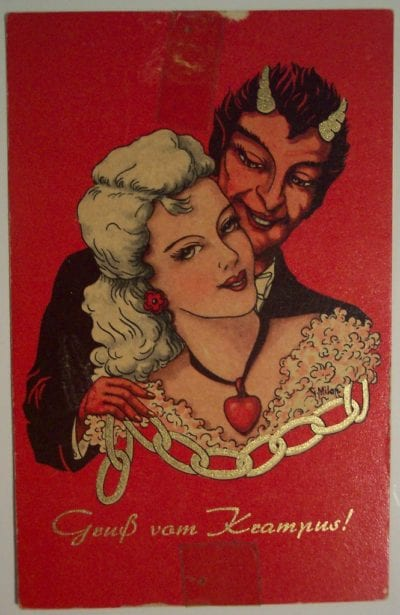 A devilish looking man with horns grins as he embraces a young woman.