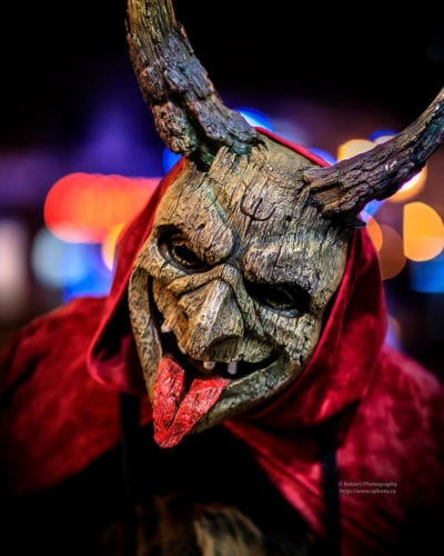 A close-up of a person wearing a horned Krampus mask.