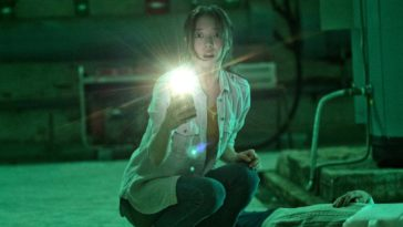 Yoo-mi shines her phones flashlight into the camera while crouching over a body in a green lit basement with a surprised action on her face