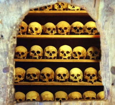 Skulls lined up on shelves behind a stone wall.