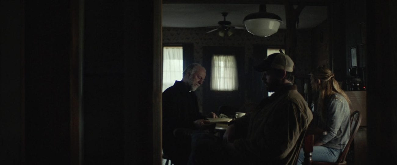 The main characters sitting at a table with a priest