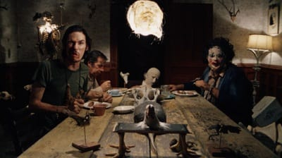 A group men sit around the dinner table. One man has a snarling expression and another wears an odd mask. At the head of the table is a corpse-like figure.