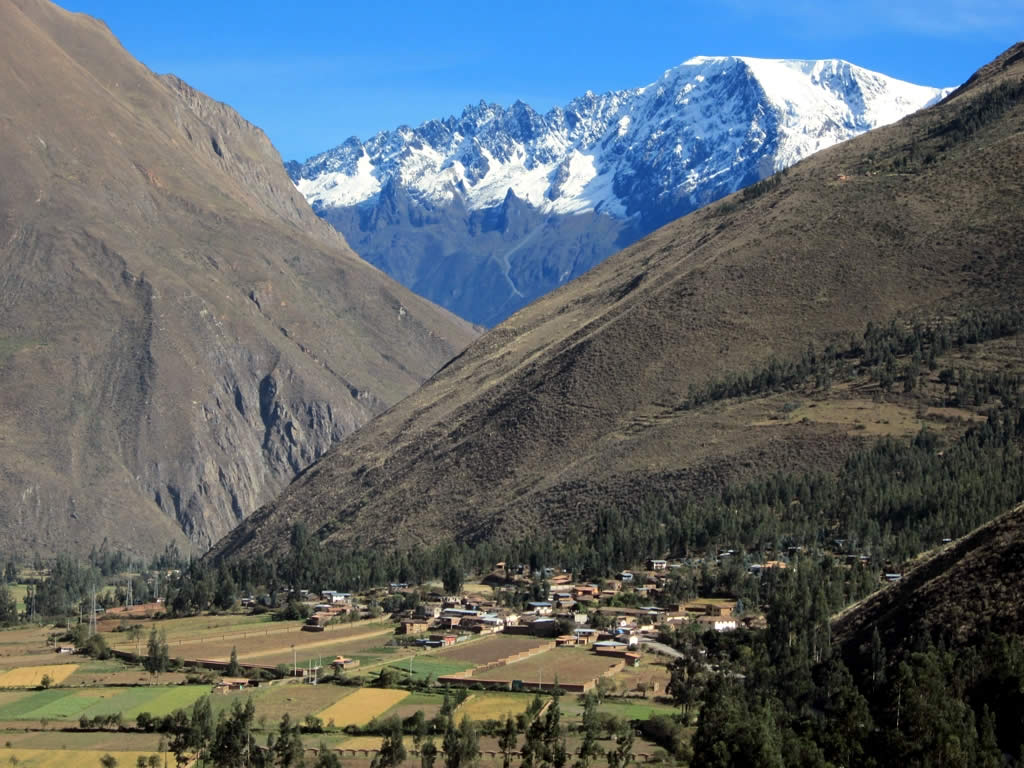 A picture of the Andes that shows a little village nestled bellow three nountain, two of which are lush and green while the third is covered with snow.