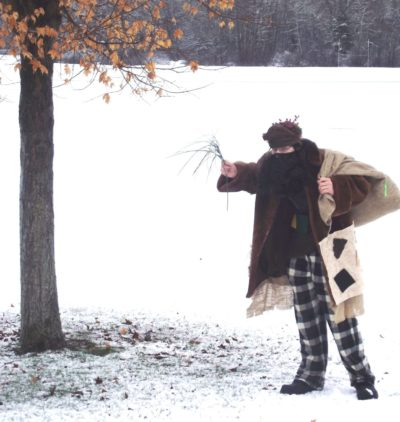 A man in modern day Belsnickel clothes holding a sack and a whip stands alone in a snow covered field.