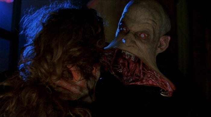 a vampire's jaw opens in an inverted triangle with pincers at the ends. he grips a person by the head with both hands