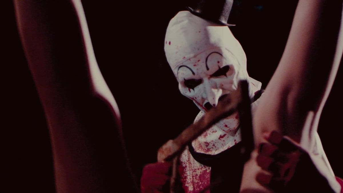 Art the Clown looking downward, his face and outfit splattered with blood, as he works a hacksaw between a pair of legs suspended upside down from the ceiling.