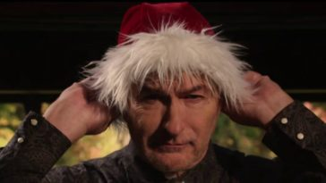 Joe Bob Briggs putting on a Santa hat
